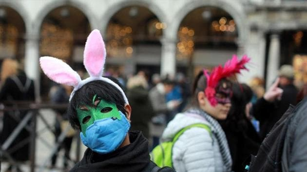 A carnival reveller wears a protective mask at Venice Carnival, which the last two days of, as well as Sunday night's festivities, have been cancelled because of an outbreak of coronavirus, in Venice, Italy February 23, 2020.(REUTERS)
