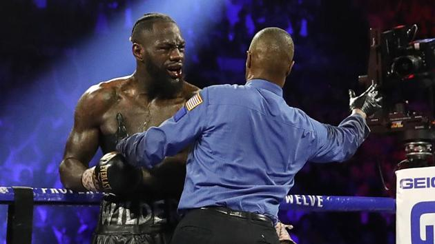 Deontay Wilder is stopped by Referee Kenny Bayless during his fight against Tyson Fury after Wilder's corner throw a towel into the ring.(REUTERS)