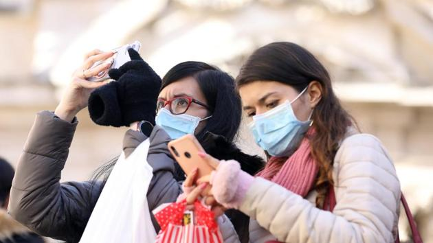 Tourists wearing protective face masks take smartphone photographs at Trevi Fountain in Rome, Italy, the worst affected European Country from novel coronavirus. Feb. 25, 2020.(Bloomberg)