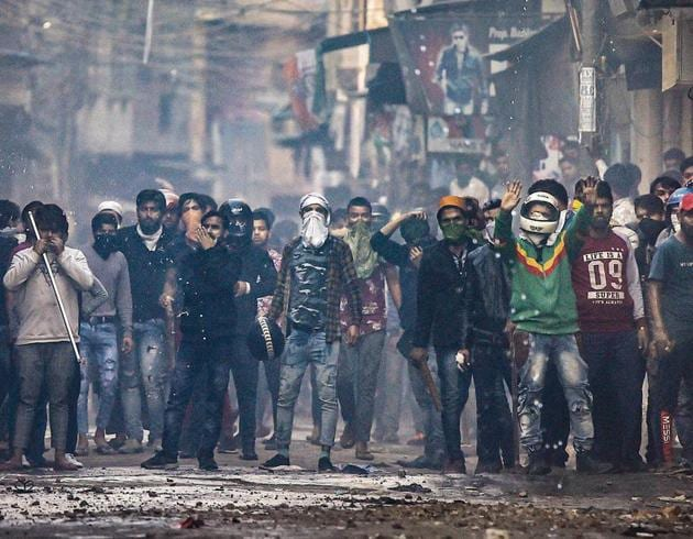 A mob armed with sticks — some of them covering their faces — can be seen during a clash in North-east Delhi on Tuesday.(Photo: PTI)