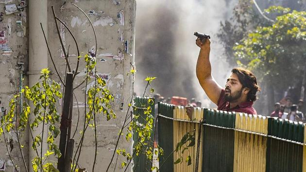 A protestor brandishes a pistol during clashes between a group of anti-CAA protestors and supporters of the new citizenship act, at Jafrabad in north-east Delhi.(PTI)