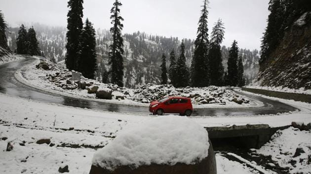 A vehicle passes during fresh snowfall on the Mughal Road, south of Srinagar.(Photo by Waseem Andrabi/ Hindustan Times)