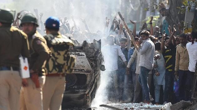 Protesters take cover from a burning car during violent clashes between anti and pro CAA demonstrations, at Jaffarabad, near Maujpur, New Delhi.(Raj K Raj/HT PHOTO)