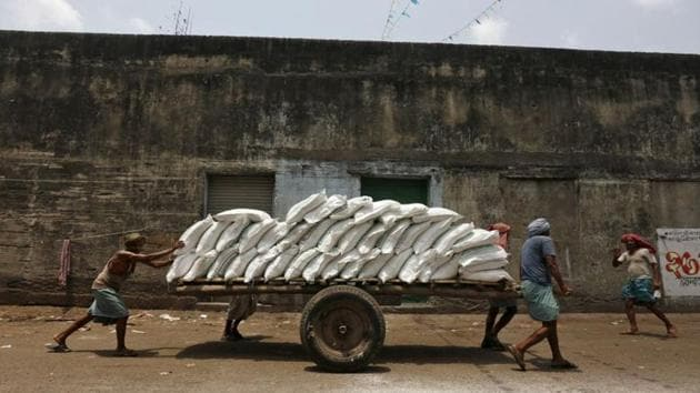 Labourers push a handcart loaded with sacks of sugar at a wholesale market in Kolkata. The latest statistics show that the current economic slowdown has been more severe than what was shown by earlier statistics.(REUTERS)
