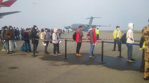 Indian nationals and foreigners stand in a queue after they were brought to India by an Indian Air Force's (IAF) C-17 Globemaster III aircraft from China's coronavirus-hit city of Wuhan, at airport in New Delhi.(PTI)