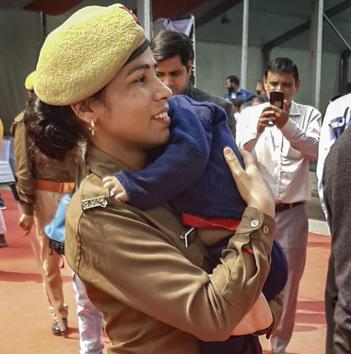 Police constable Priti Rani arrives on duty with her 18-month-old son during UP Chief Minister Yogi Adityanath's event, in Noida.(PTI)