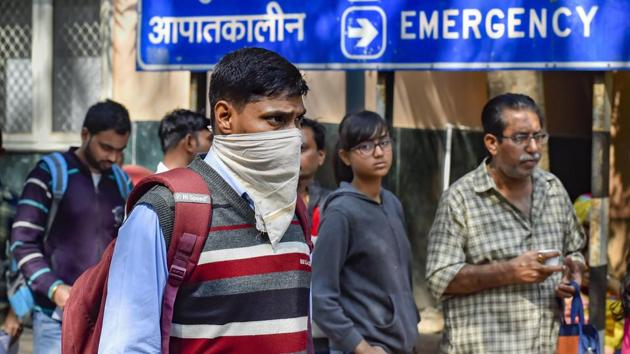 A man uses a handkerchief to cover his face in the wake of coronavirus outbreak, at RML Hospital in New Delhi on Tuesday.(PTI Photo)