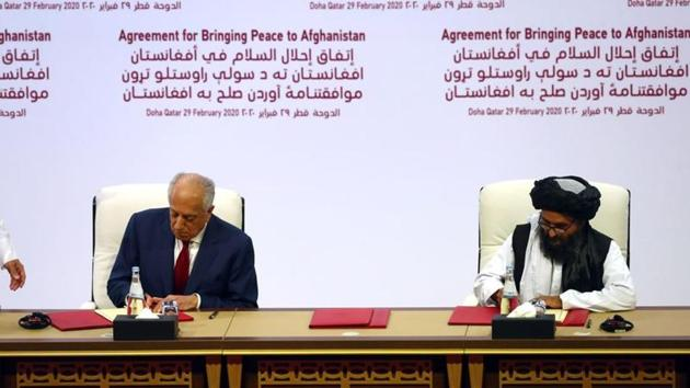 Mullah Abdul Ghani Baradar, the leader of the Taliban delegation, signs an agreement with Zalmay Khalilzad, US envoy for peace in Afghanistan, at a signing agreement ceremony between members of Afghanistan's Taliban and the US in Doha, Qatar.(REUTERS)