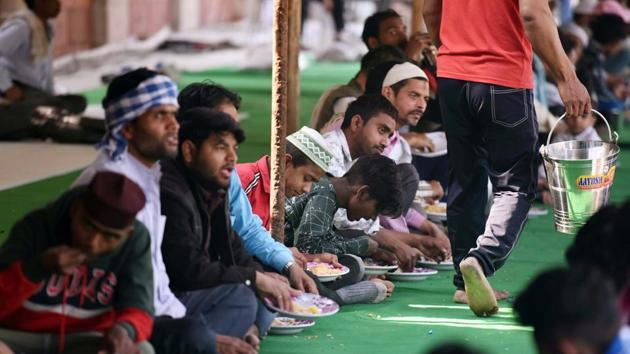 People are seated in rows to partake food in a relief camp for individuals affected in last week's violence that erupted in north-east Delhi over the Citizenship Amendment Act (CAA), at Idgah Masjid, Mustafabad, in New Delhi.(Raj K Raj/HT PHOTO)