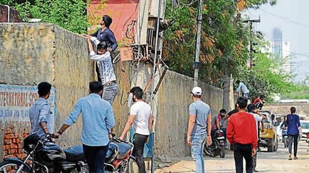 Youths try to scale the wall of a government school in Gurugram on Tuesday.(HT)