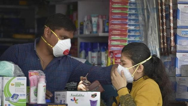 A salesmen at a chemist shop in New Delhi helps a buyer wear her protective mask, in wake of the deadly coronavirus, on Wednesday.(PTI Photo)