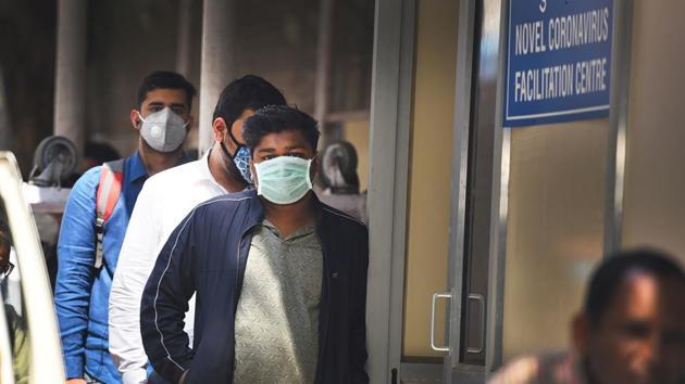 People wearing protective masks stand in a queue near novel coronavirus Facilitation Centre at Ram Manohar Lohia (RML) Hospital following positive cases of coronavirus in the country in New Delhi on Wednesday.(Raj K Raj/HT PHOTO)