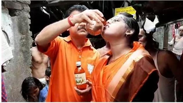 BJP leader Narayan Chatterjee feeding cow urine to a woman during an event in Kolkata on Monday.(HT Photo)