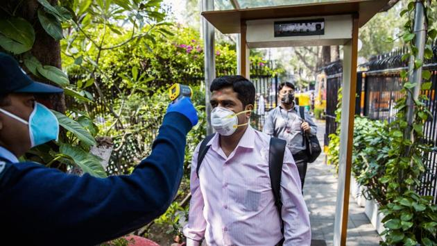 An office worker wearing a protective mask is screened with an infrared thermometer as he enters a building in New Delhi.(Bloomberg)