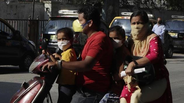 A family travels on a scooter wearing protective masks as a precaution against coronavirus in Mumbai, on Tuesday.(AP Photo)