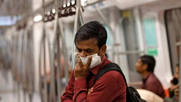 A commuter uses his handkerchief to cover his face as he travels in a metro amid coronavirus fears, in New Delhi on March 17.(Reuters Photo)