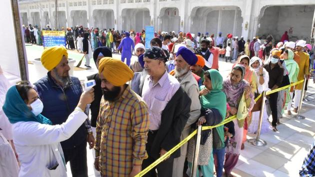 A medic wearing a face mask screens devotees at the main entrance of the Golden Temple.(Sameer Sehgal/Hindustan Times)
