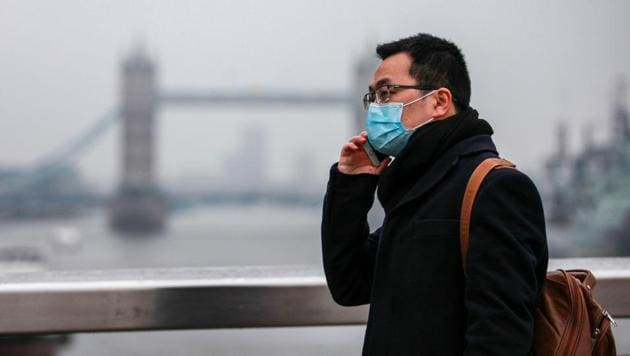Covid 19: A commuter, wearing a protective face mask, crosses London Bridge in view of Tower Bridge in London, UK.(Bloomberg)
