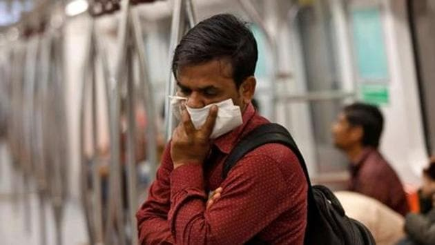 A commuter uses his handkerchief to cover his face as he travels by metro in NCR.(REUTERS PHOTO.)
