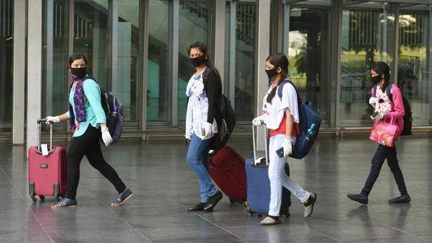 Passengers wearing protective masks in the wake of coronavirus pandemic, walk out of the Kolkata airport.(PTI)