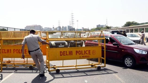 Policemen stop and check ID cards of Commuters on the Gurgaon-Delhi border after lockdown in Gurgaon on Monday. Indian capital Delhi locked down from March 23 to 31st due to the coronavirus outbreak and borders with Delhi remain sealed during the period.(ANI)