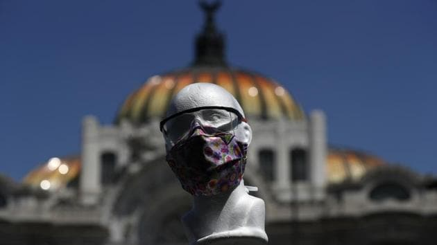 A styrofoam head models a handmade fabric face mask being sold by Jorge Rodriquez, in front of the Palace of Fine Arts in Mexico City.(AP)