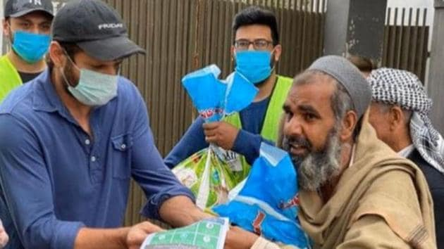 Former Pakistan captain Shahid Afridi hands out essentials to people while doing community service amid the coronavirus pandemic.(Twitter)