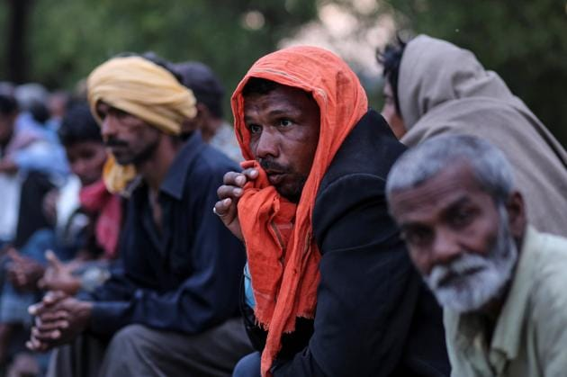 Daily wage workers and homeless people wait for food outside a government-run night shelter during a 21-day nationwide lockdown to limit the spreading of coronavirus disease (COVID-19), in New Delhi.(REUTERS)
