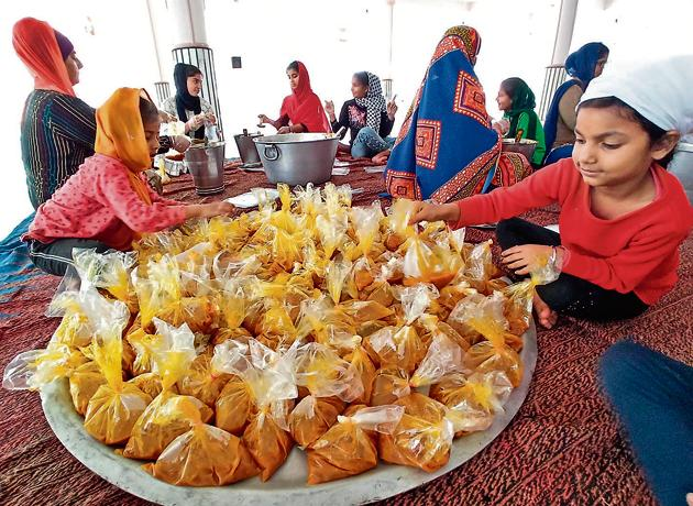 Children helping out in packing food, to be distributed among the needy and homeless,at the Sector 19 gurdwara in Chandigarh. Each of the 5,000 packets dispatched by gurdwaras in the tricity had three chapatis and one cooked vegetable.(RAVI KUMAR/HT)