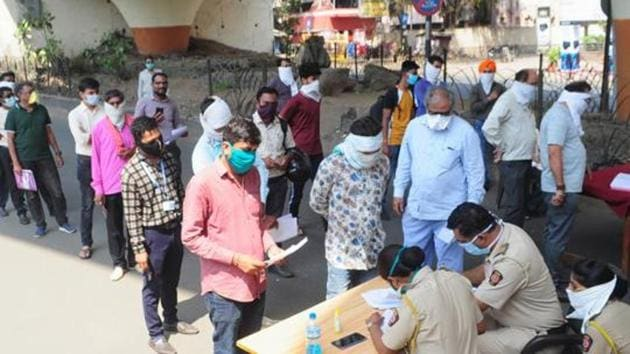 People maintain social distance as they stand in a queue to collect passes for essential services during day-2 of a nationwide lockdown, imposed in the wake of coronavirus pandemic, in Nagpur on March 26, 2020.(PTI file photo)