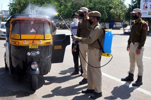 A policeman sanitising an auto-rickshaw during lockdown in Jammu on Sunday(Nitin Kanotra)
