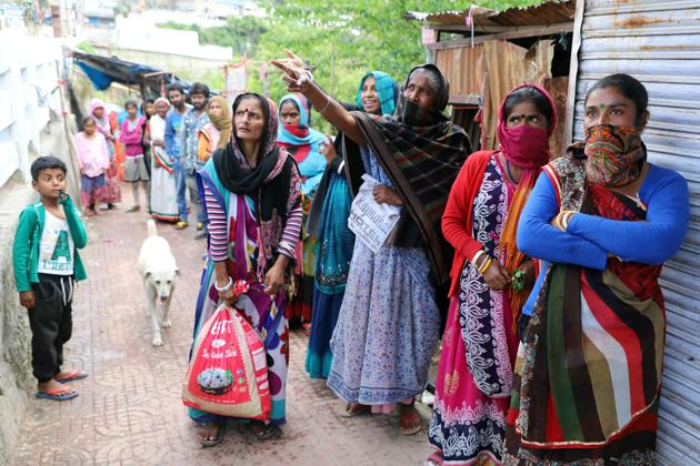People carrying goods distributed by the district administration in Mandi on Sunday.(Birbal Sharma)
