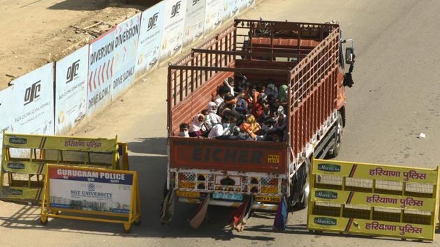 Migrant workers head home in a goods truck at the Gurugram-Alwar national highway, NH 248, near Tau Devilal Stadium, Sector-38, in Gurugram. (Parveen Kumar / HT Photo)