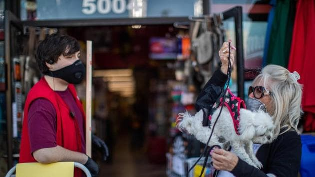People wearing masks as a preventive measure against the spread of the COVID-19 novel coronavirus, in front of a hardware store in Long Beach, California(AFP/Apu GOMES)