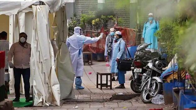 A volunteer wearing protective suit checks temperature of a man at Nizamuddin during coronavirus lockdown in New Delhi.(ANI)