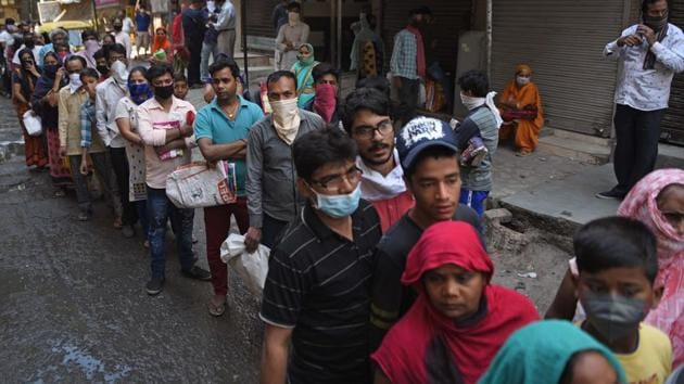People queue up to take foodgrains from a government PDS shop, on Day 6 of the 21-day nationwide lockdown, at a locality in New Delhi on Monday.(Sanchit Khanna/HT Photo)