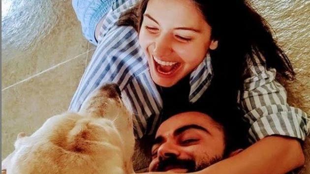 Anushka Sharma and Virat Kohli with their dog.