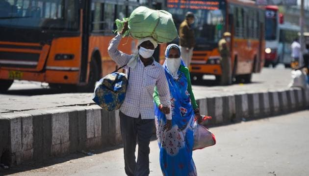 Migrant workers head home on Day 5 of the 21 day nationwide lockdown imposed by PM Narendra Modi to curb the spread of coronavirus, outside Anand Vihar Bus Terminus, in New Delhi, India, on Sunday, March 29, 2020.(Amal KS/HT PHOTO)