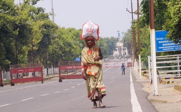 An elderly woman carry belongings on her head as she walk past the Odisha assembly inBhubaneswar during the lockdown to contain the spread of COVID-19, March 25, 2020.(ANI File / Representational Photo)