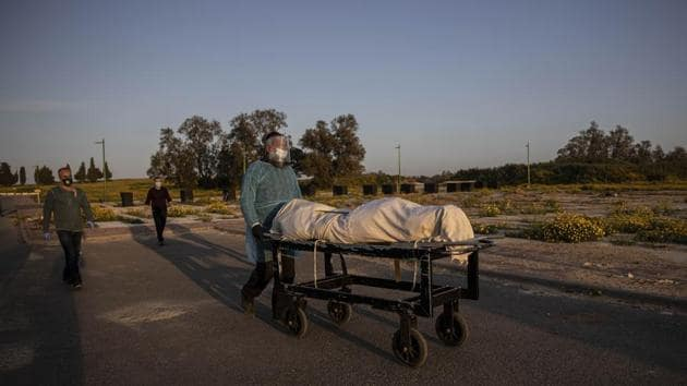 A member of Hevra Kadisha, an organization which prepares bodies of deceased Jews for burial according to Jewish tradition, pushes a body during a funeral of a Jewish man who died from coronavirus in the costal city of Ashkelon, Israel.(AP)