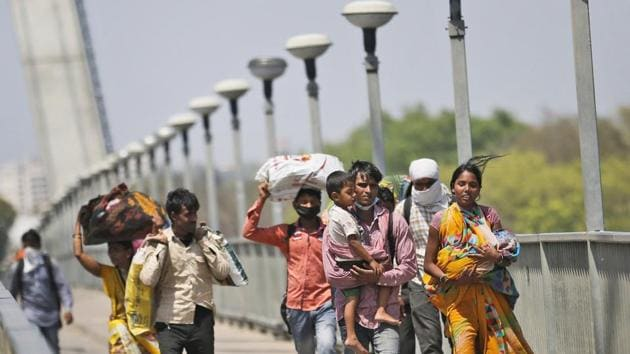 Daily wage laborers holding their children walk on foot to their respective villages following a lockdown amid concern over spread of coronavirus, on the outskirts of Prayagraj, India.(AP)