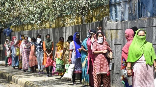 People queue while maintaining distance during a food distribution at Govt Boys Sr. Sec School No. 4, on day twelve of the 21-day nationwide lockdown to check the spread of coronavirus, in Sarojini Nagar, New Delhi.(Arvind Yadav/HT PHOTO)