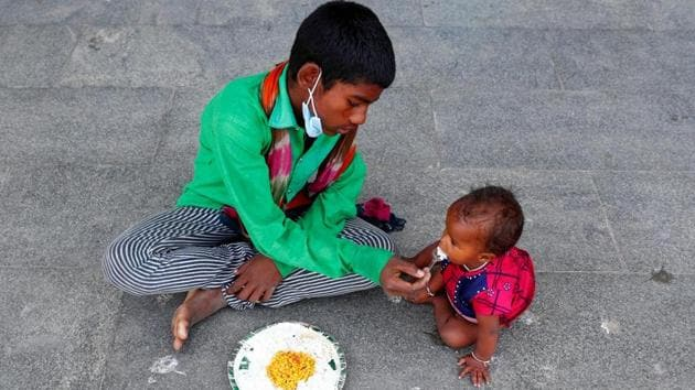 A homeless boy feeds his sister.(Reuters)