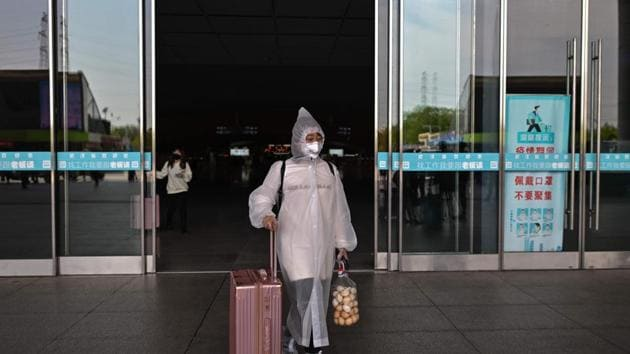 A woman wearing protective clothes and a face mask arrives at the railway station in Wuhan, in China's central Hubei province on April 6, 2020.(AFP)