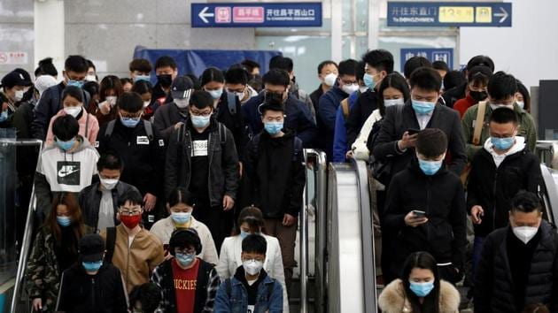 People wearing face masks stand on an escalator inside a subway station during morning rush hour in Beijing, on April 7.(Reuters Photo)