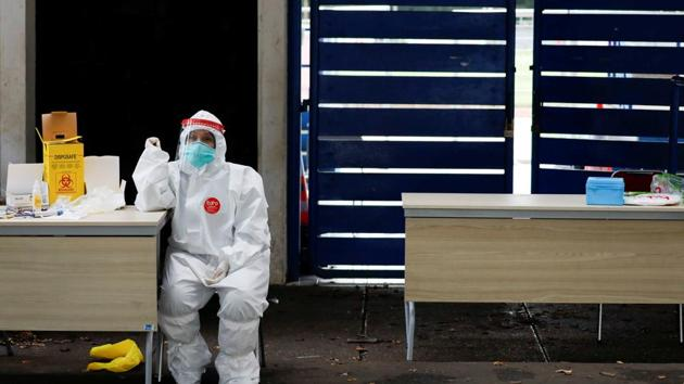 A healthcare worker wearing protective gear waits to test people for the coronavirus disease (COVID-19) outside a stadium in Bogor, West Java province, Indonesia.(REUTERS)
