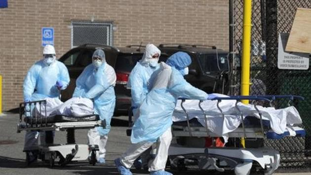 Healthcare workers wheel the bodies of deceased people during the outbreak of the coronavirus disease (COVID-19) in the Brooklyn borough of New York City, New York, US, April 6, 2020.(REUTERS)