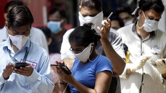 People in protective masks buying essentials during the nationwide lockdown in Mumbai.(ANI PHOTO.)