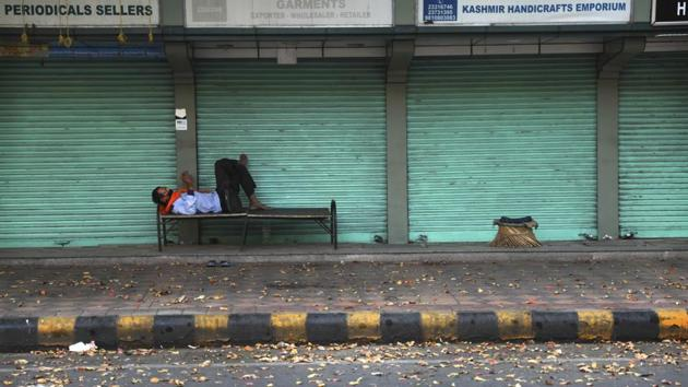 A private security guard checks his mobile phone while resting in front of closed market during the nation wide 21 day lockdown amid concern over the spread of coronavirus in New Delhi, India.(AP)
