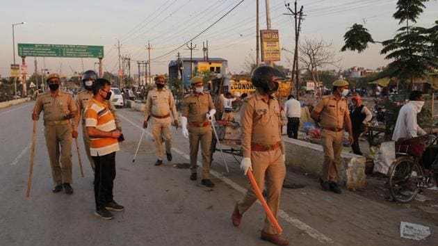 Policemen ask vegetable vendor to leave a market during lockdown to check the spread of the coronavirus, in Prayagraj. Image used for representational purpose only.(AP)